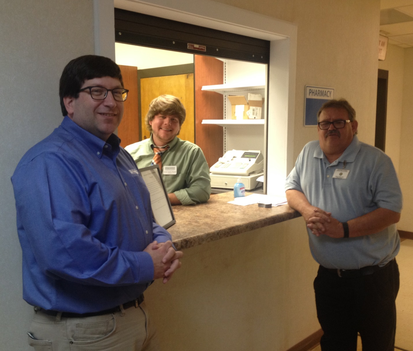 Philip Boyd, president of SPS, Jeremy Smith, pharmacist, and Dale Cottle, NWAMHC executive director.