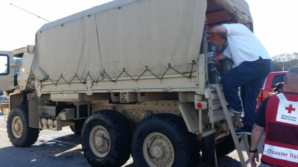Employees load medication totes onto a NCNG truck.